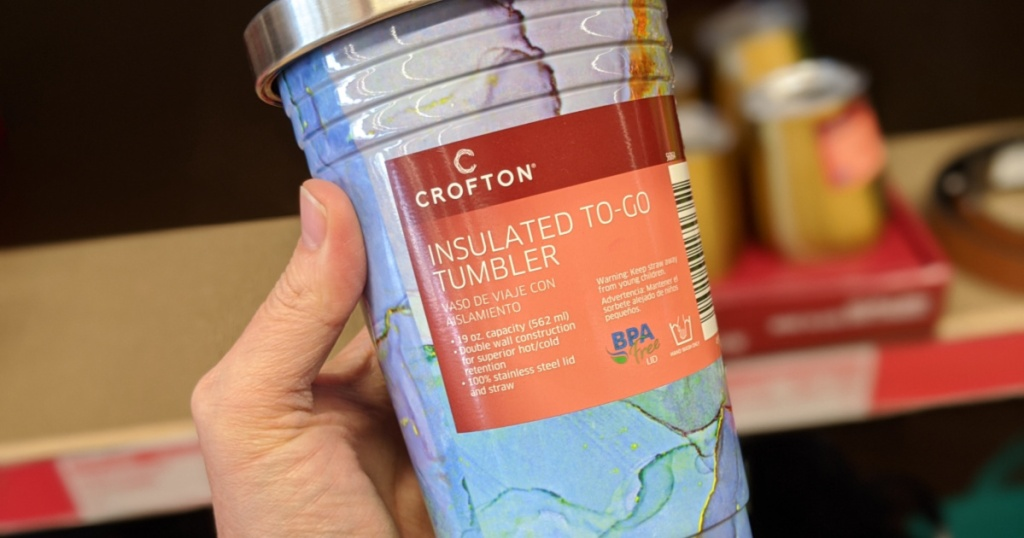 woman hand holding marbled purple, blue, and some green insulated to-go tumbler