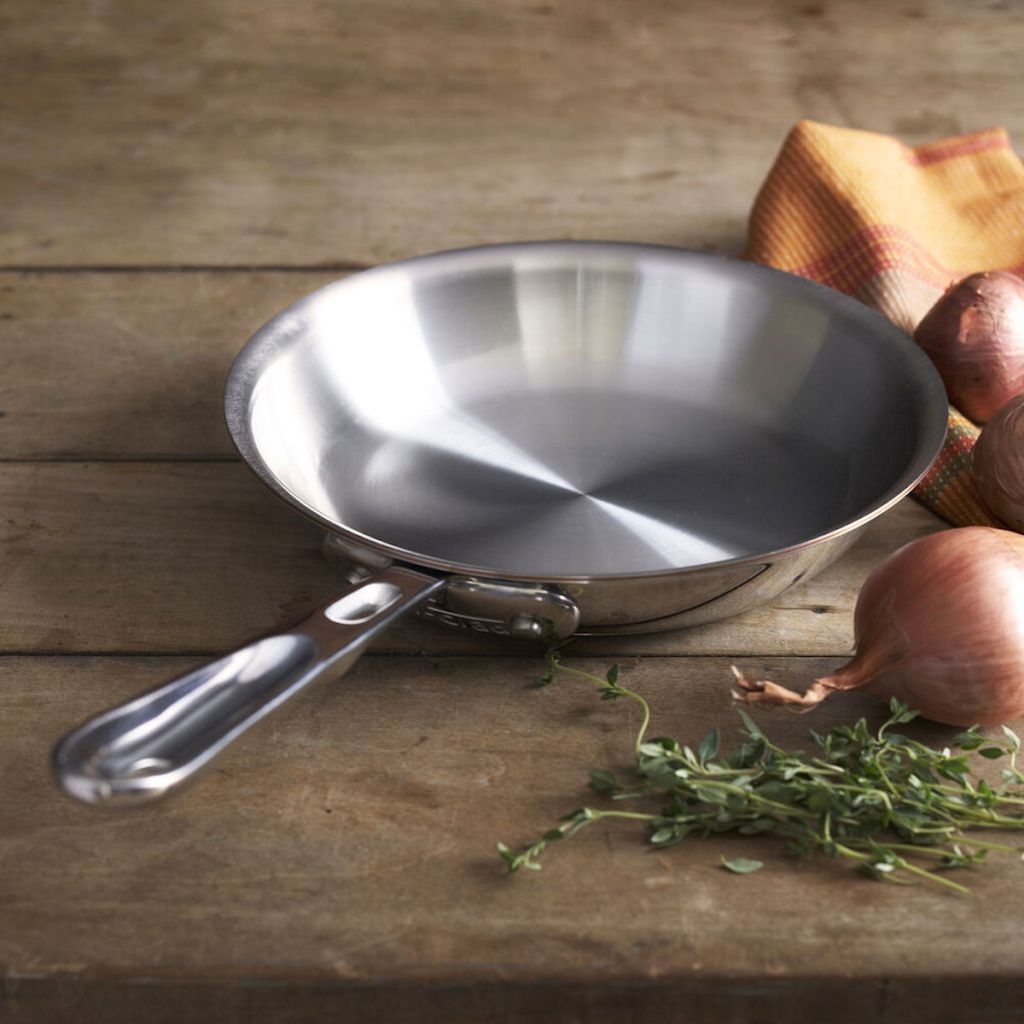 empty All Clad 12-In. Fry Pan with Copper Core with onions, cloth, and herbs next to it
