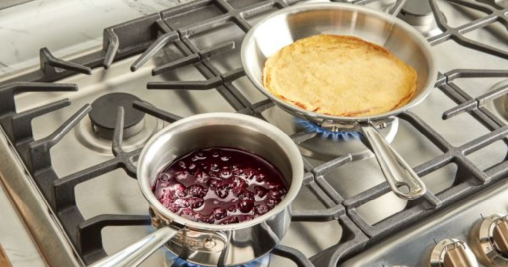 stainless steel all clad frying pan with crepe and sauce pan with blueberries on gas range