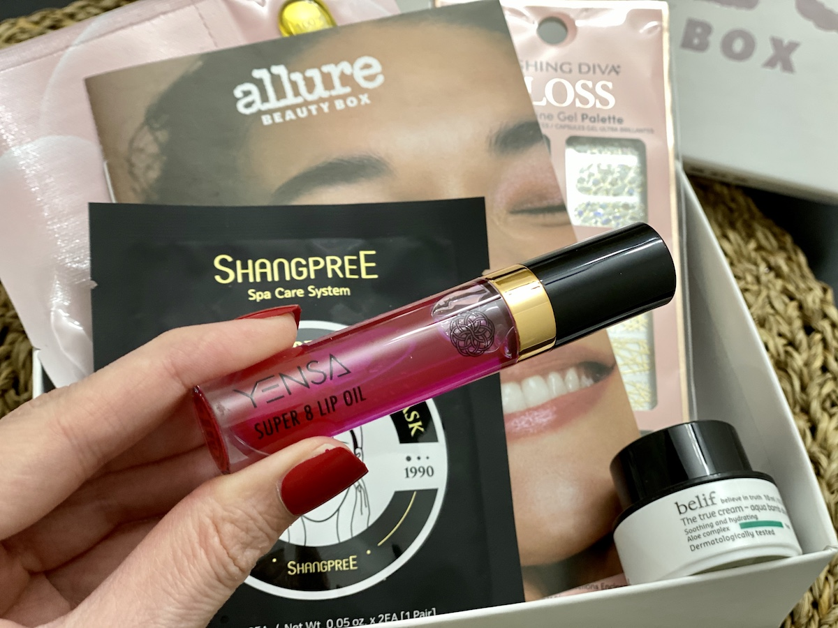 hand holding Yensa lip oil in front of Allure beauty box
