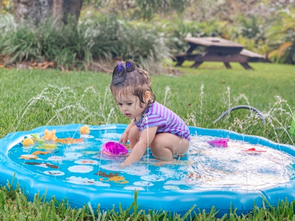 little girl squatting and playing in a blue colored splad pad with water flowing