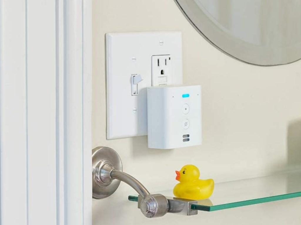 white plug-in mini smart speaker in outlet in bathroom