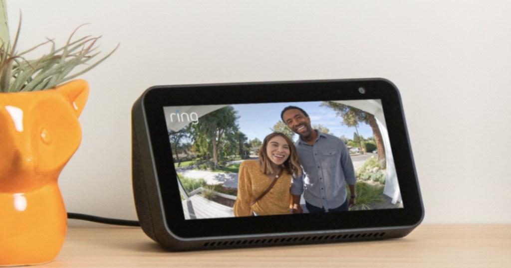 perangkat pintar hitam yang menunjukkan rekaman kamera pintar di atas meja di sebelah pabrik