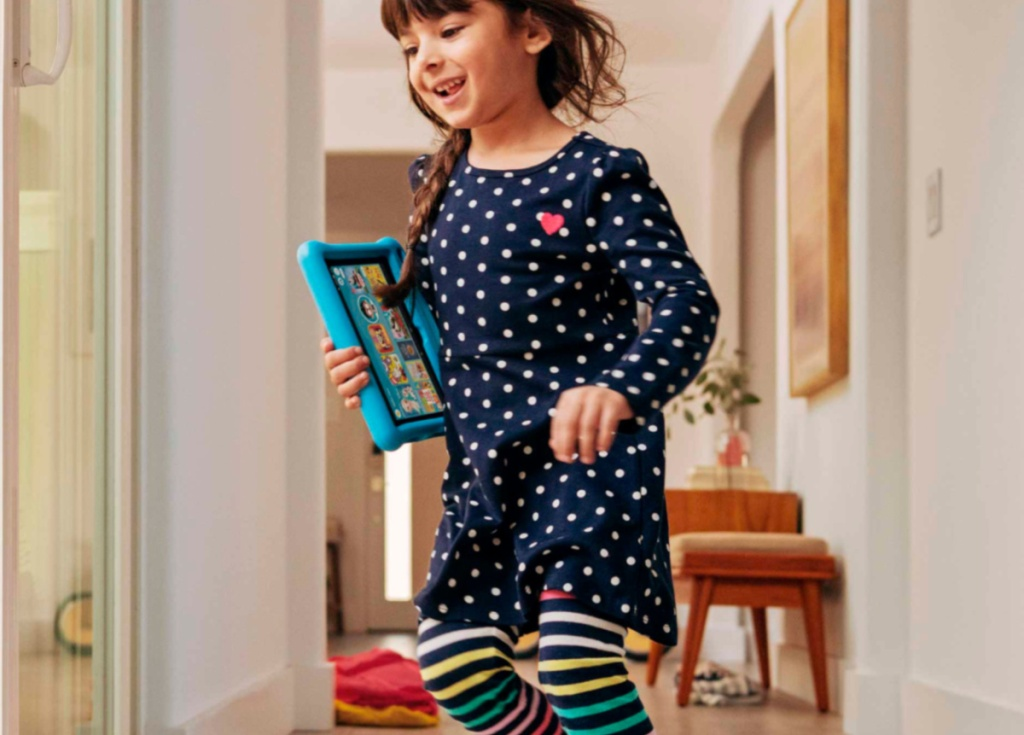 girl holding blue kindle fire while walking through the house