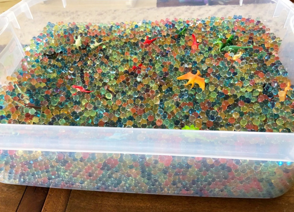 clear plastic container filled with water beads in assorted colors with plastic toys mixed in