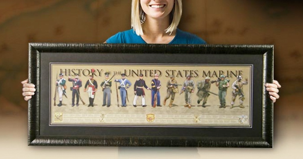women holding a framed poster of the history of the US marines