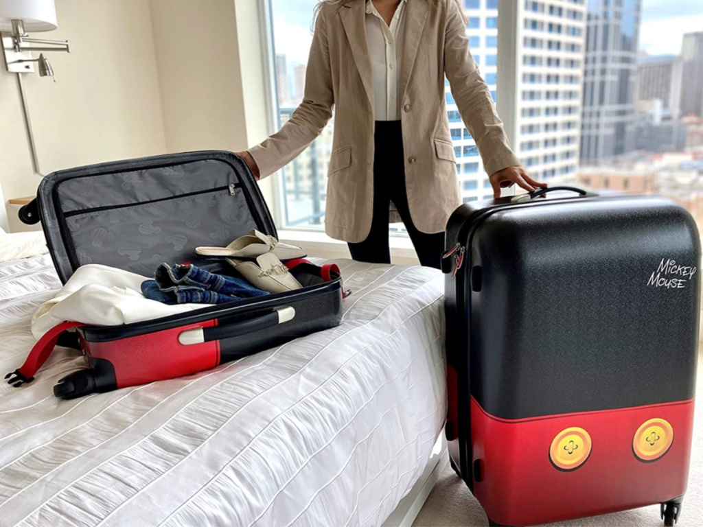 woman in hotel room with Disney themed luggage on bed