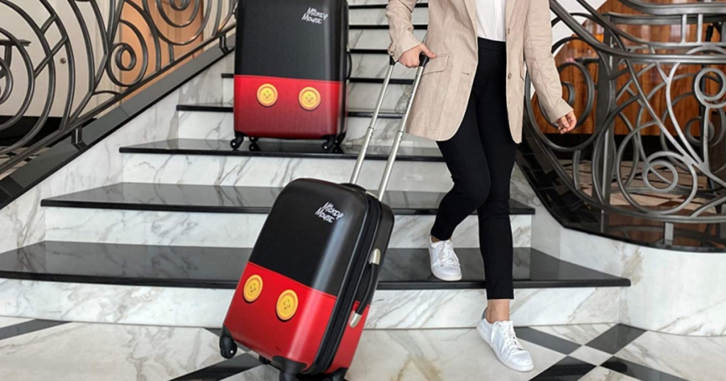 woman walking down large set of steps with Disney themed luggage