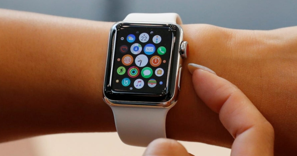 finger touching white smart watch on wrist