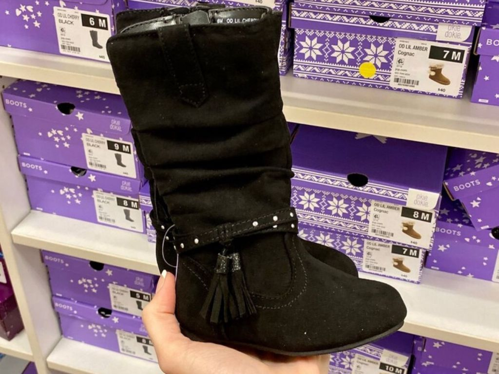 woman's hand holding tall suede kids boots