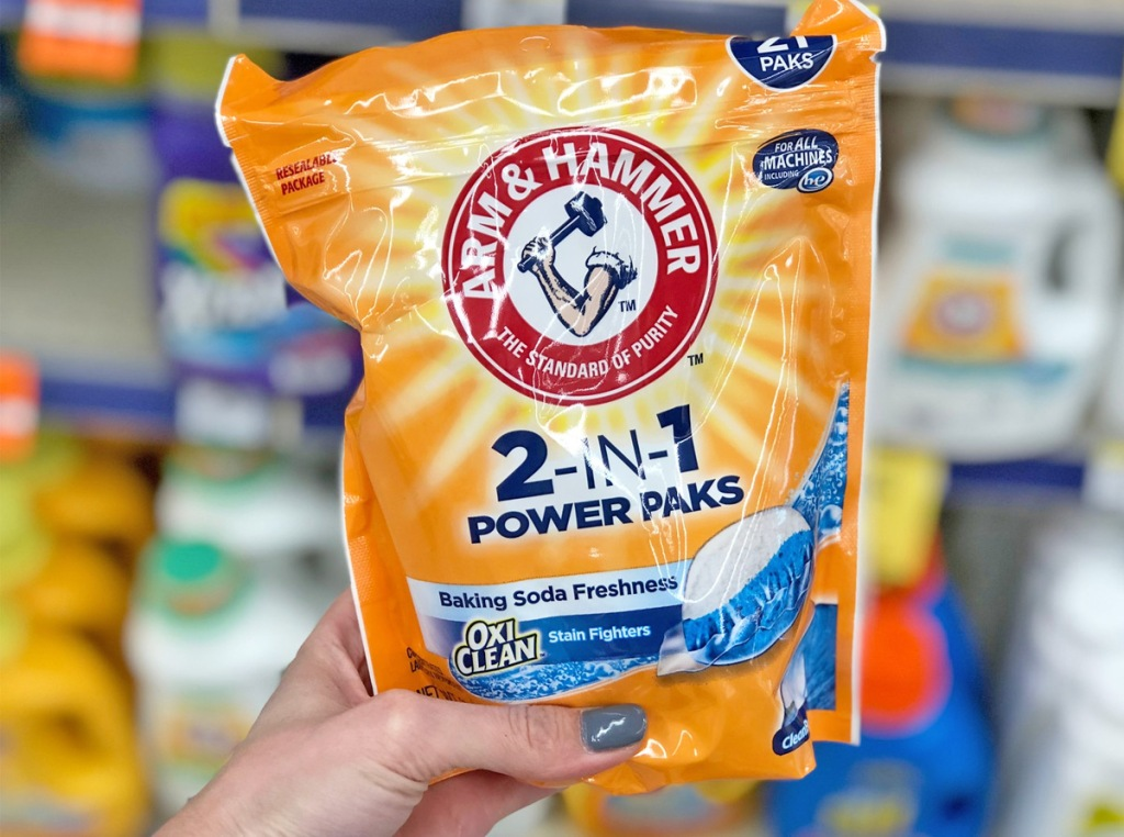 person holding up an orange bag of arm & hammer laundry detergent pods