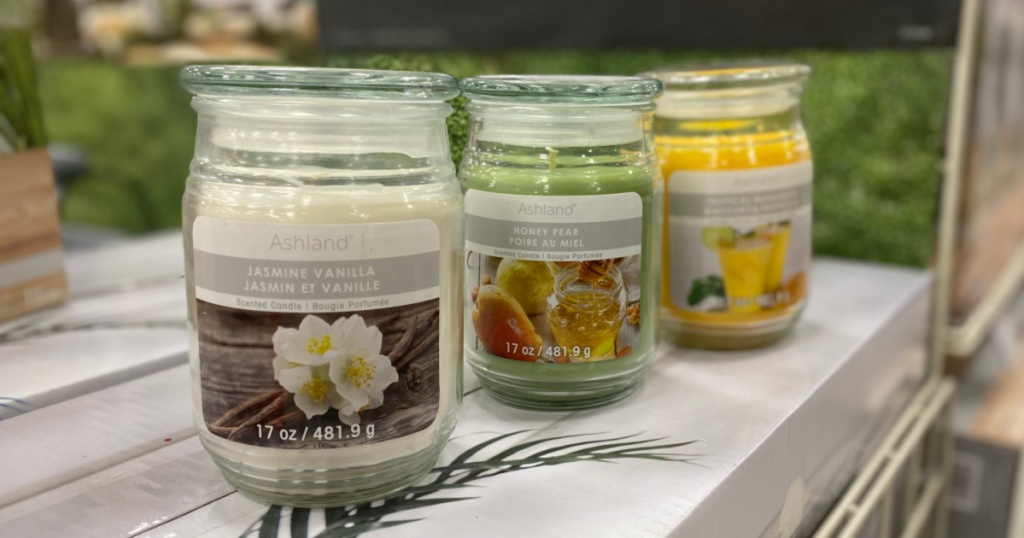 three scented jar candles on counter in store