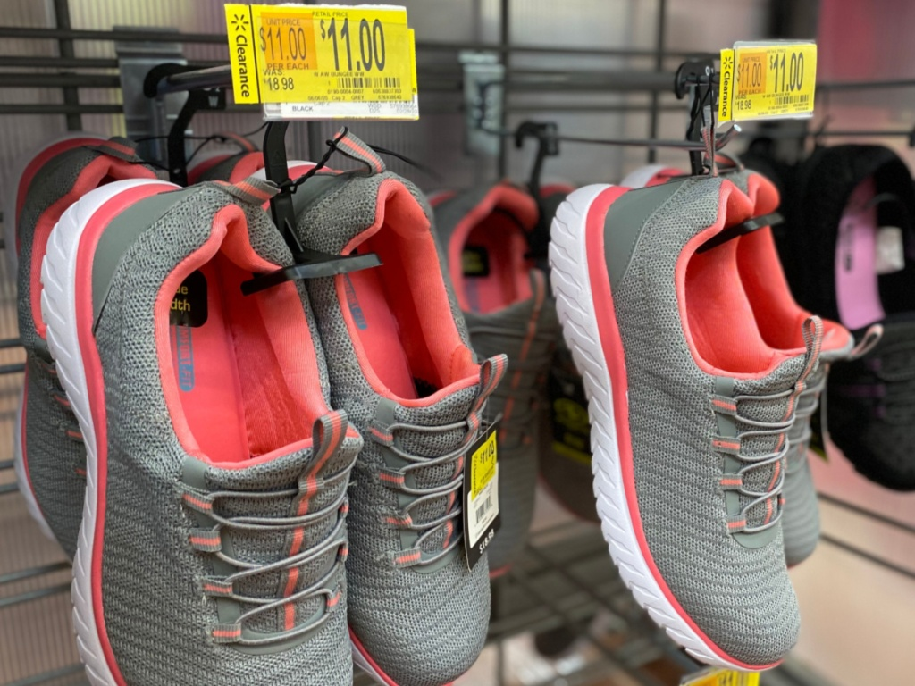 women's gray and pink sneakers hanging in store
