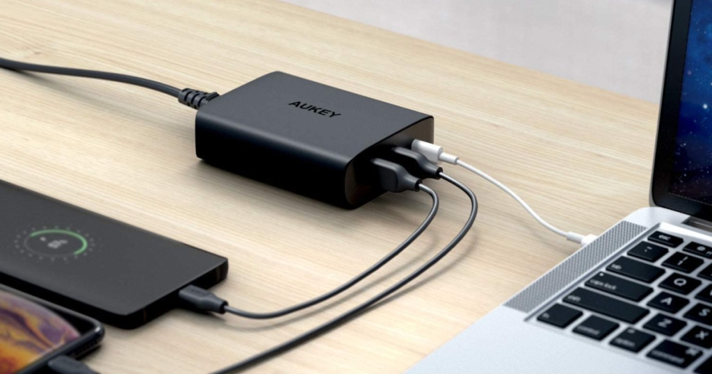 Aukey charger plugged into iphones and macbooks