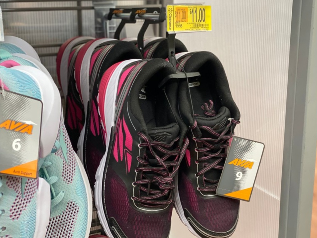 women's black and pink running shoe hanging in store