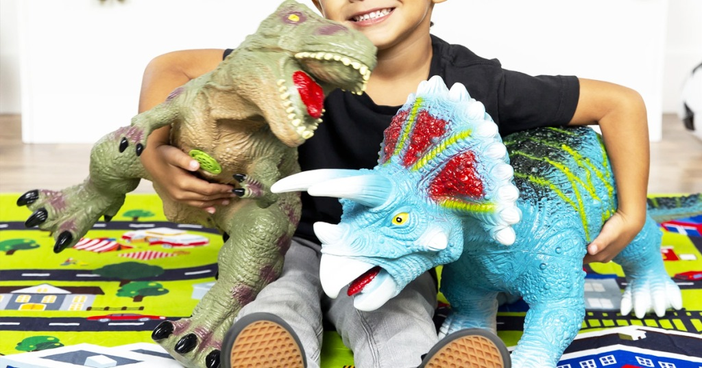 child sitting on playroom floor with arms around green t-rex and blue triceratops dinosaur toys