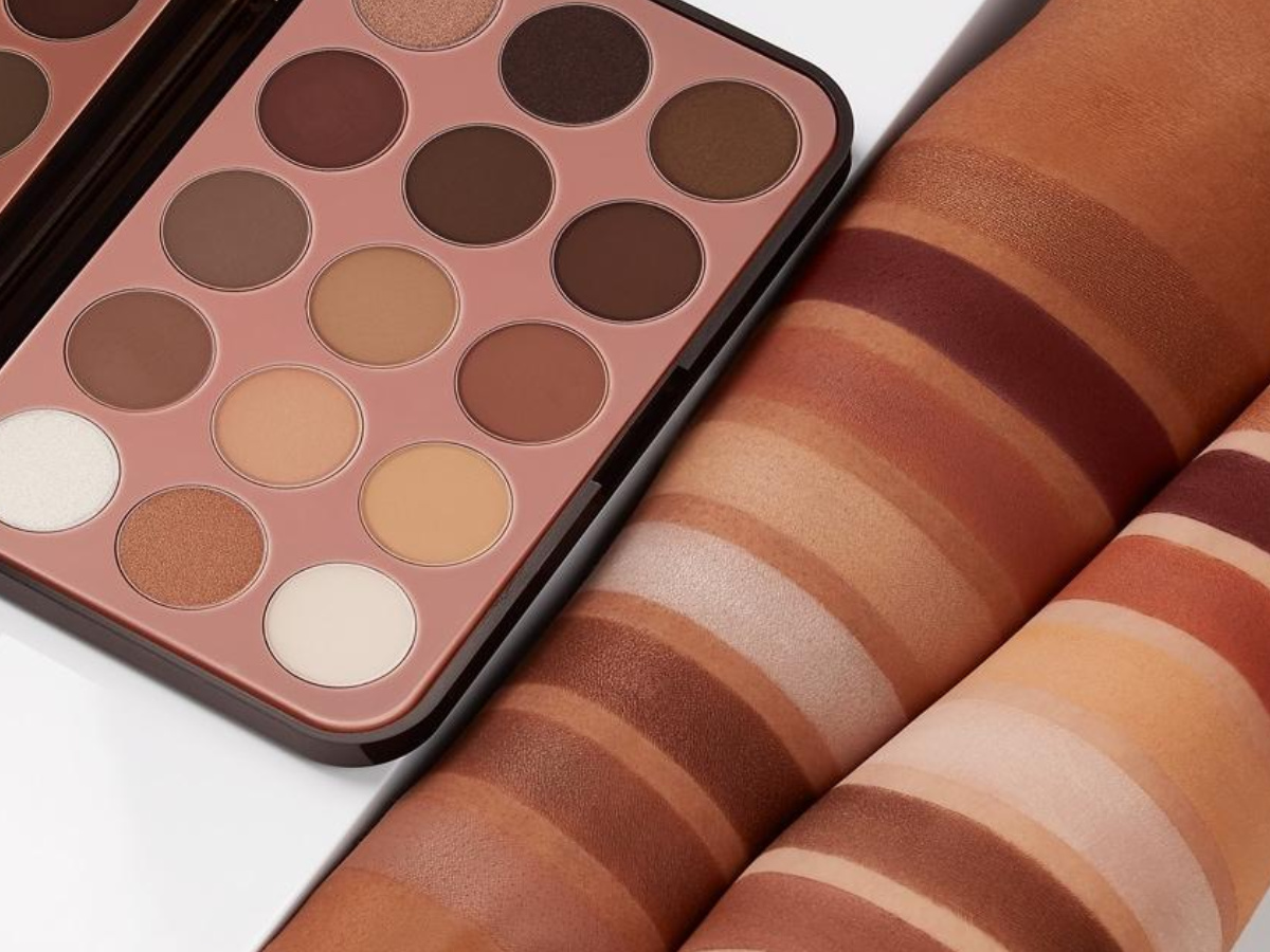 2 arms with makeup on them sitting next to a skintone eyeshadow palette