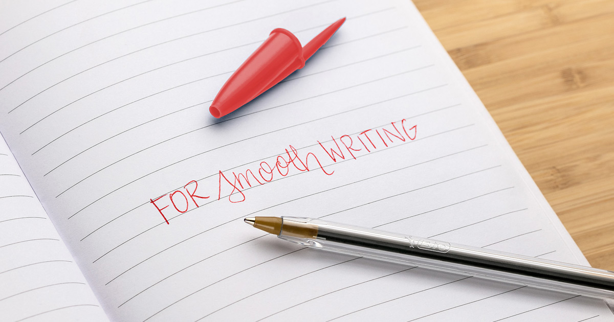 """pen and red cap laying on notebook with """"for smooth writing"""" printed in red ink on page"""