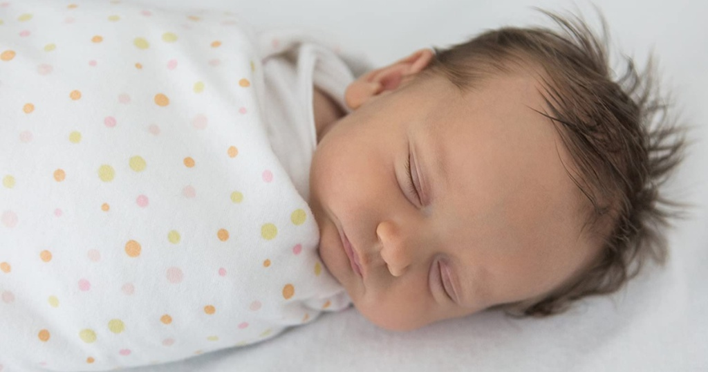 baby sleeping with white and pink polka dot swaddled