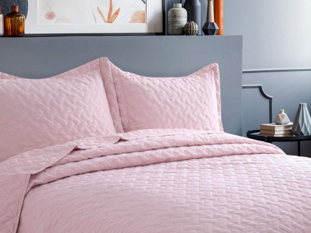 light pink quilt set on a grey bedframe next to a side table with books and nicknacks