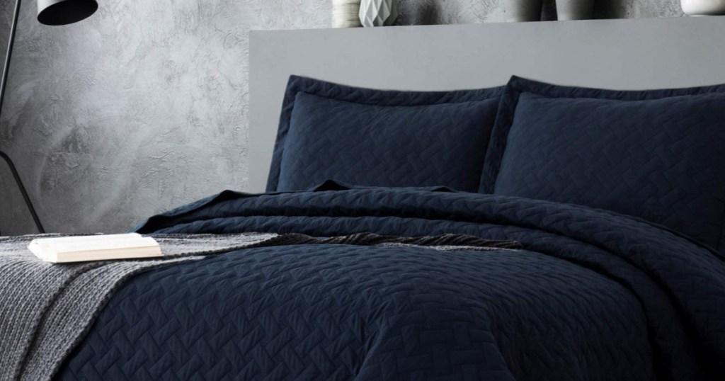 navy blue quilt set on a grey bedframe