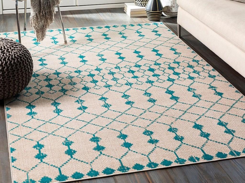 beige and teal diamond rug on wooden floor in living room