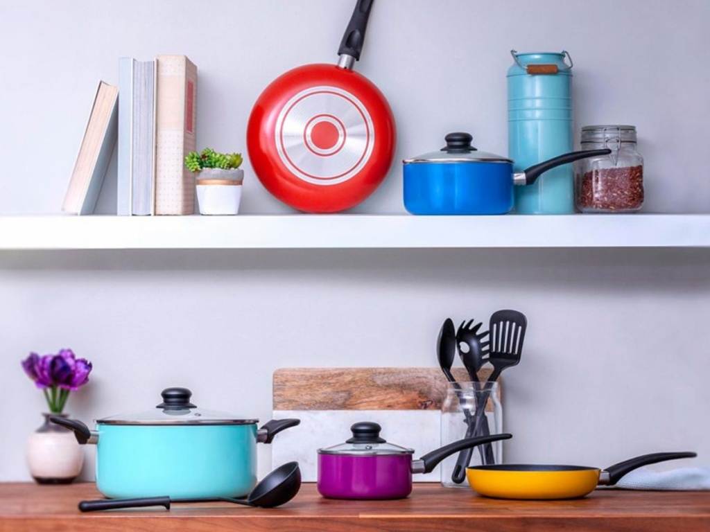 colorful cookware set on wood counter and shelf in home