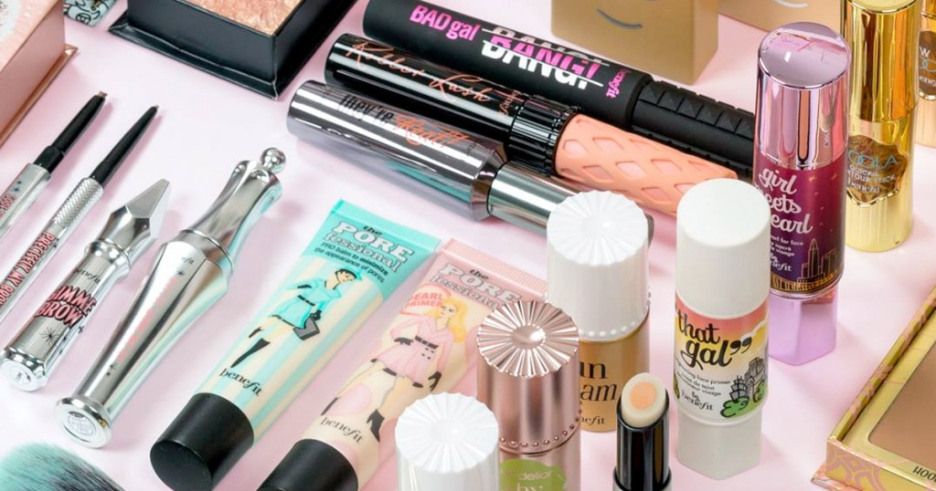 benefit primers, mascaras, and highlighters laying on a pink background