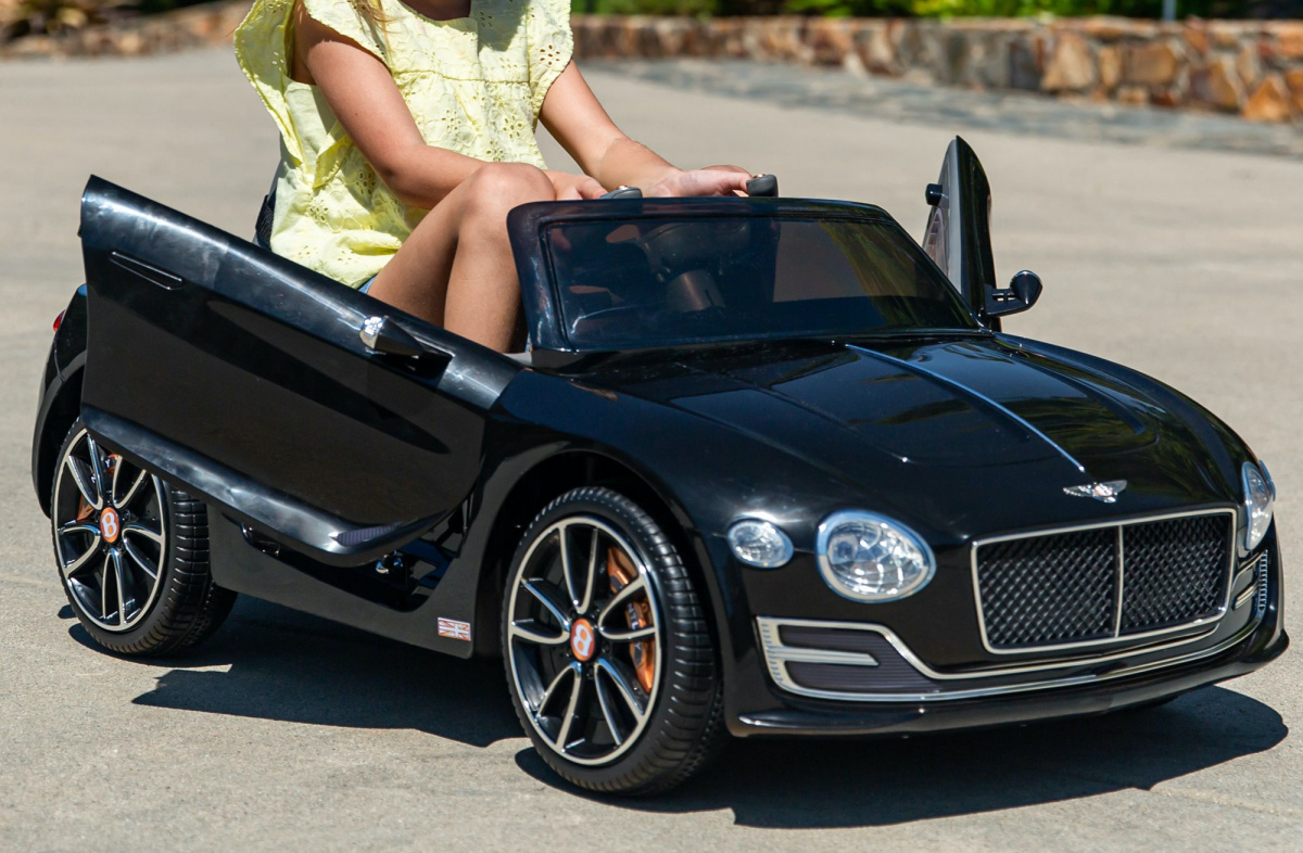 girl in black Bently ride-on car outside