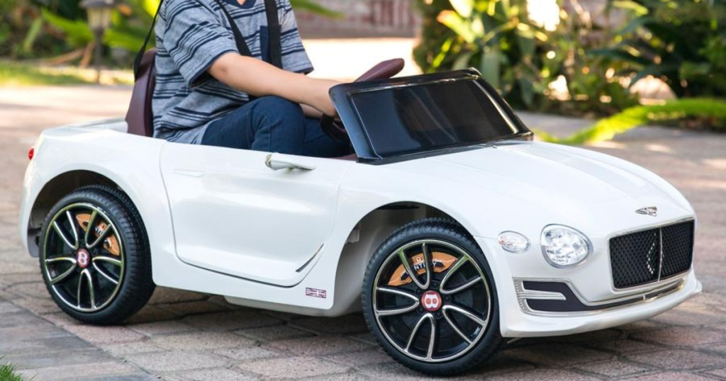 boy in white Bently ride-on car outside
