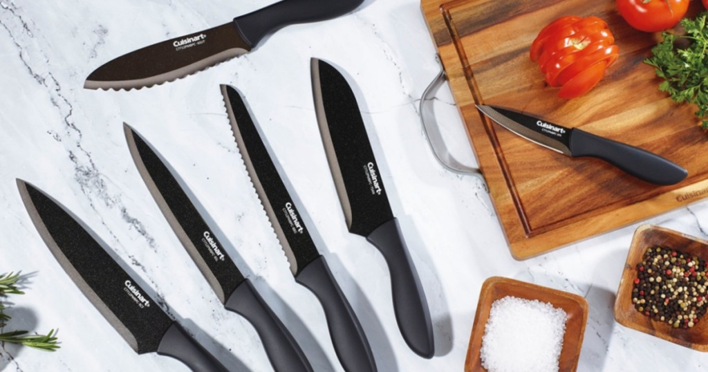 assorted black knives on marble counter top and cutting board