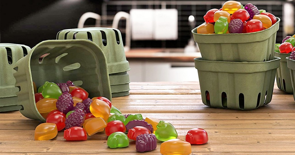 fruit containers filled with fruit shaped snacks on wood table