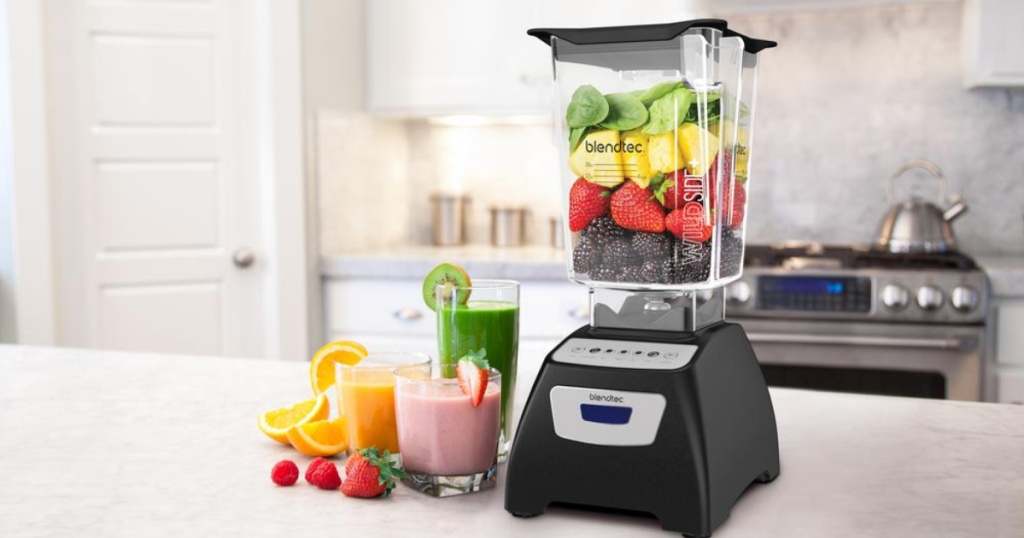 Blendtec Classic 570 Blender on counter with fruit inside of it and smoothies to the side