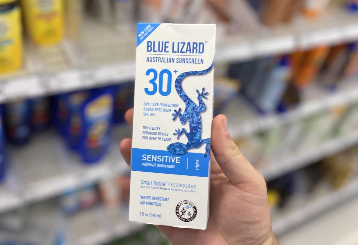 hand holding blue lizard sunscreen box inside target