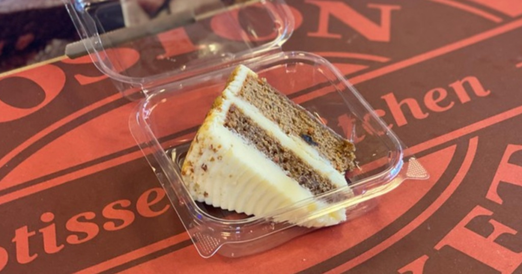 slice of boston market carrot cake on table in to go plastic container