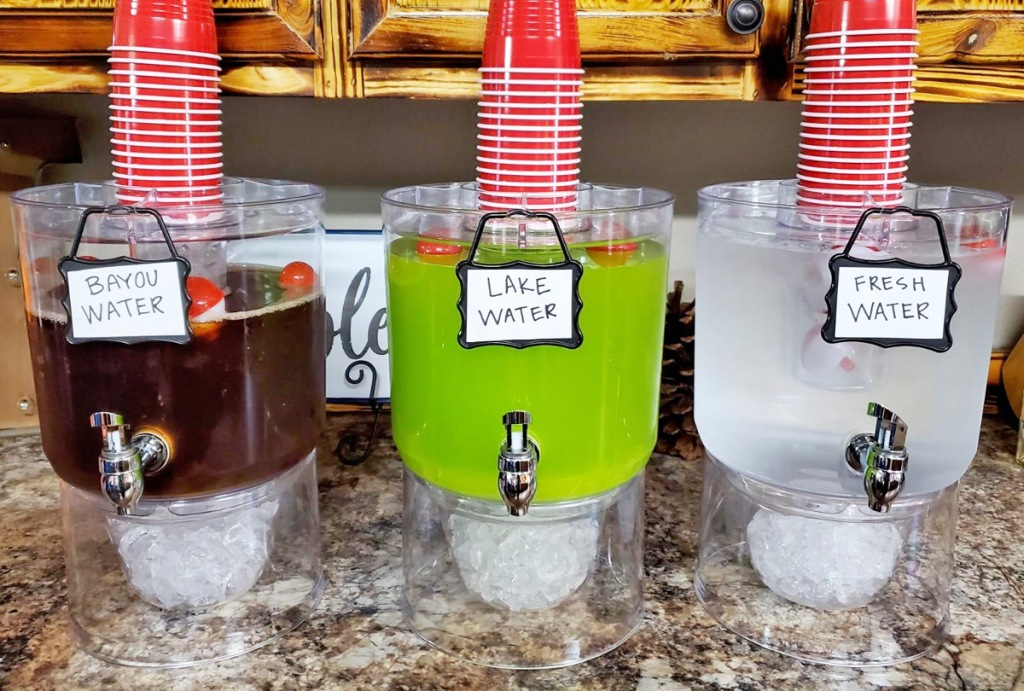 three clear beverage dispensers with different colored drinks inside and red plastic cups stacked on top