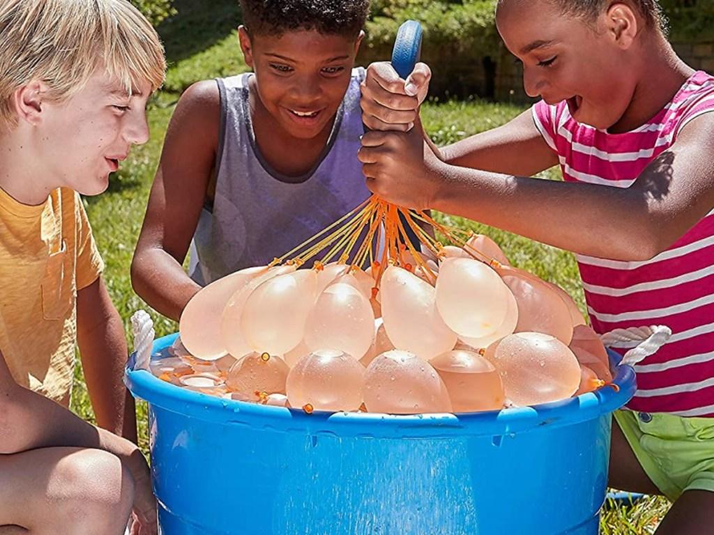 three children around tub of orange water-filled balloons