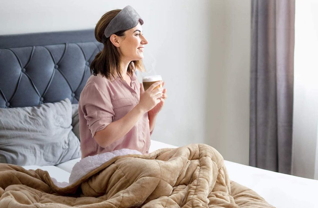 woman sitting on a bed holding a coffee