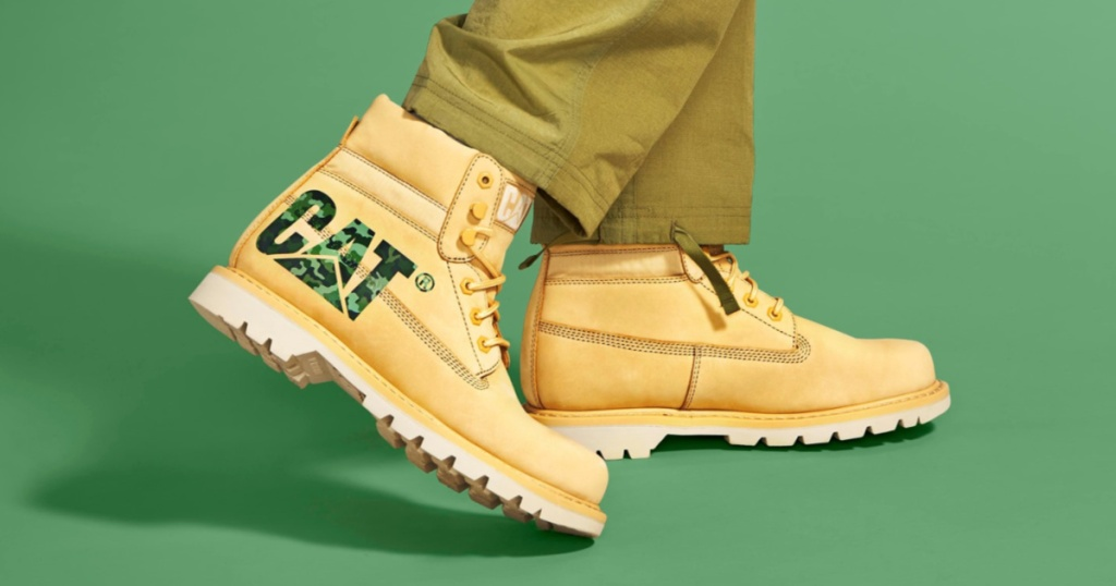 person wearing tan boots with green brand logo and green background