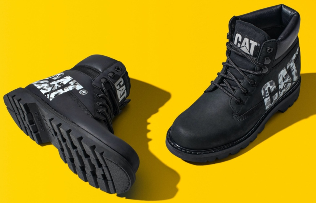 black boots with white brand logo and yellow background