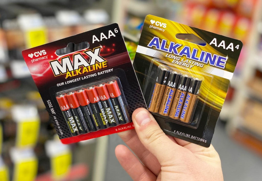 person holding up two packages of CVS brand AAA batteries