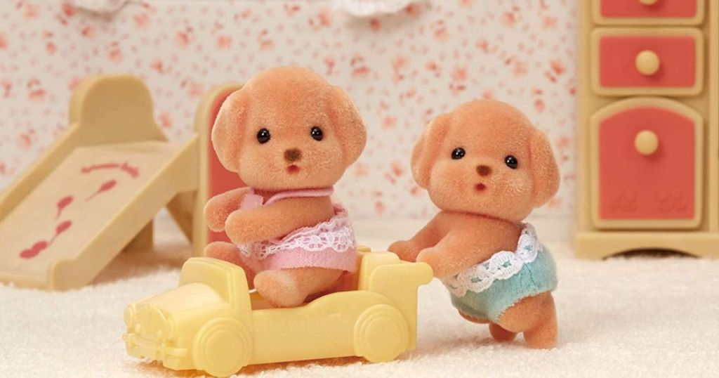 two puppy toy figures playing on a plastic toy car