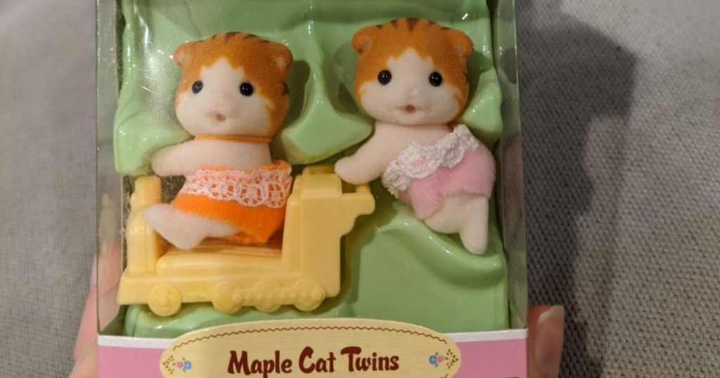 two tiny cat figurines in a box