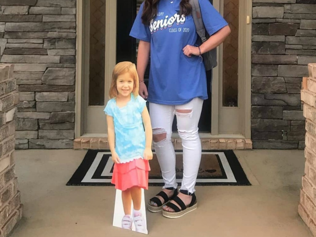 cardboard cutout of a little girl standing next to girl in a doorway