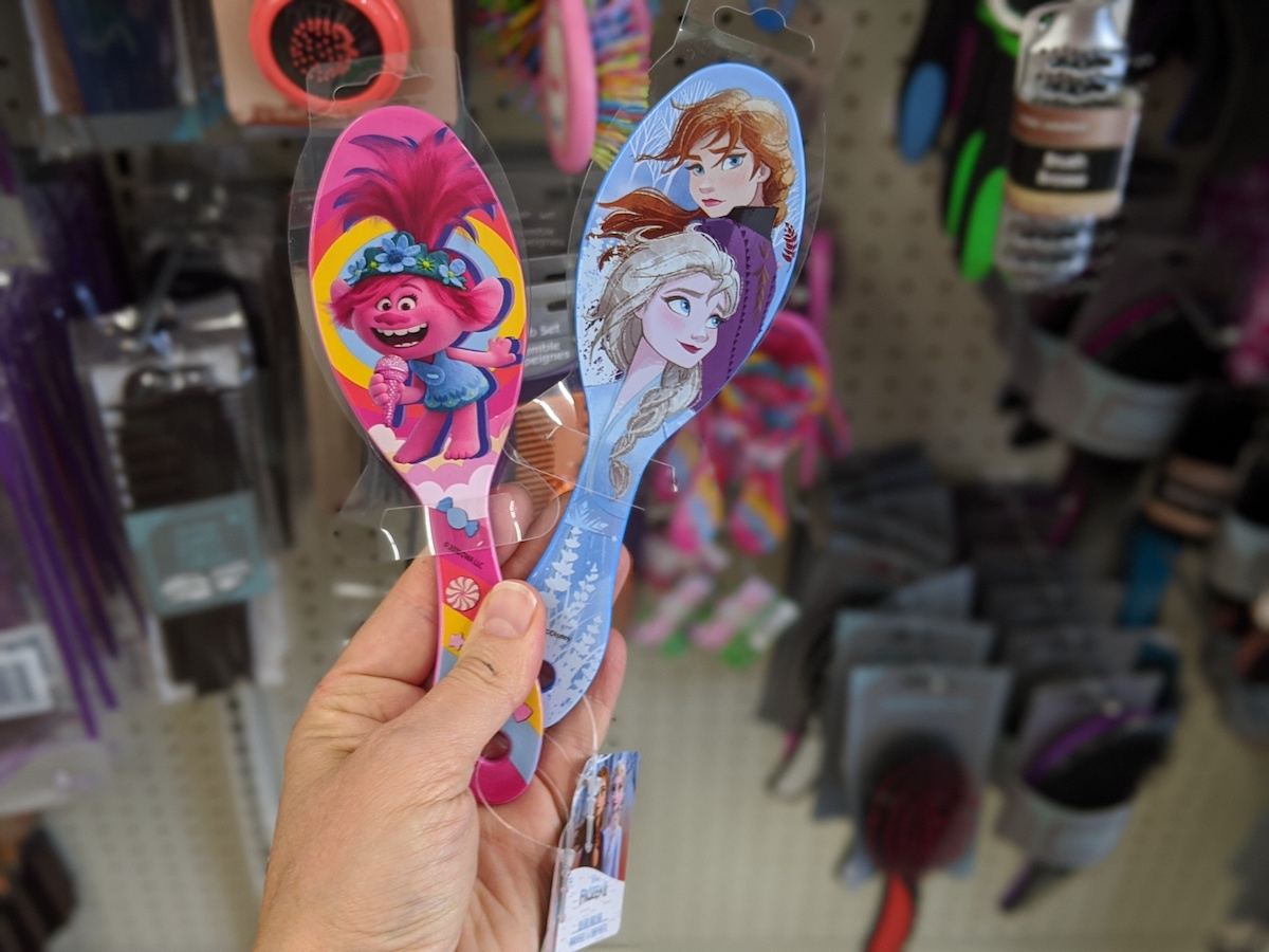 hand holding two Character Hairbrushes