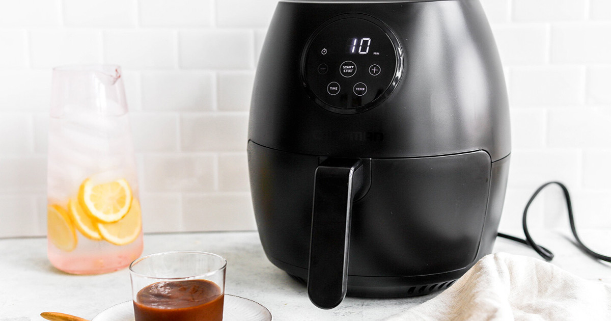 Best Air Fryer - black air fryer with digital display sitting on counter next to pitcher of lemonade