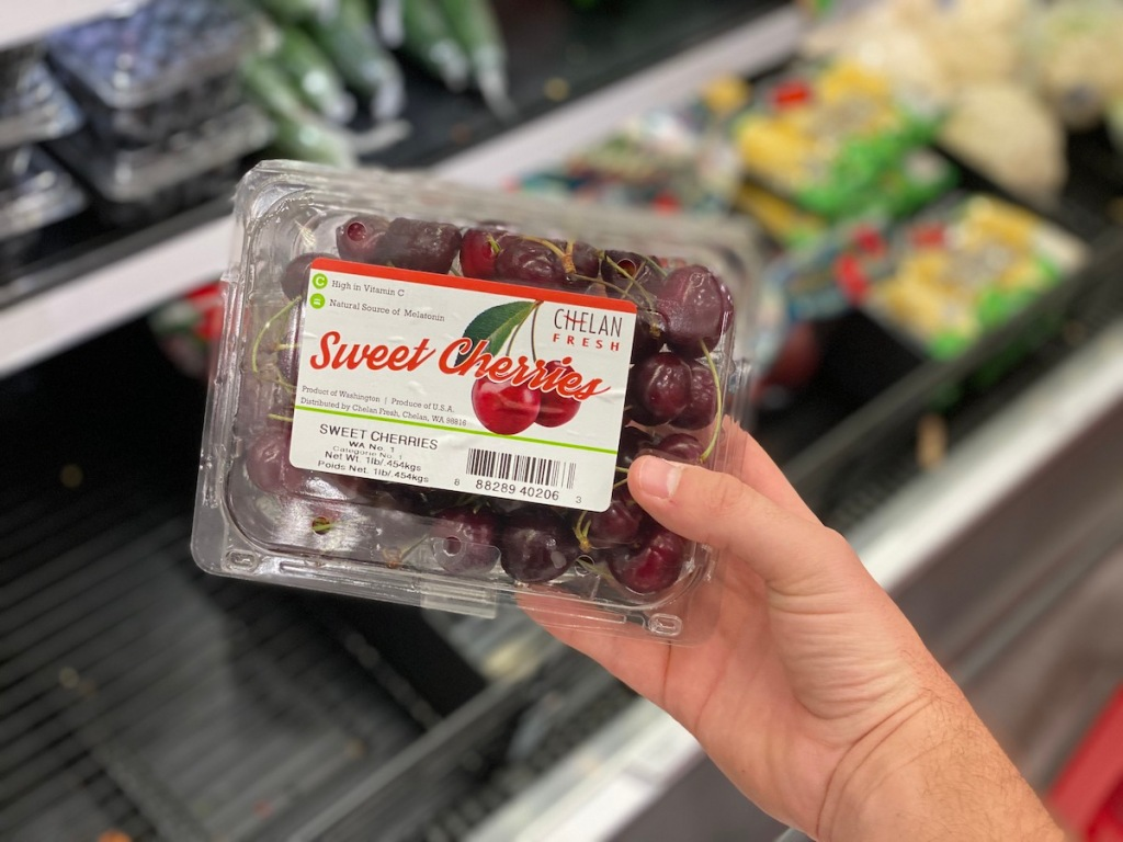 man hand holding container of fresh cherries at target