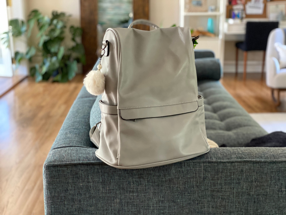 silver backpack purse sitting atop of blue/grey couch