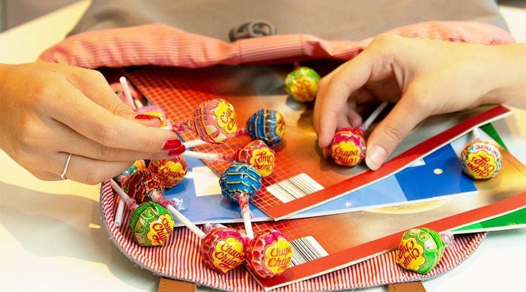 hands reaching into bag for Chupa Chups lollipops