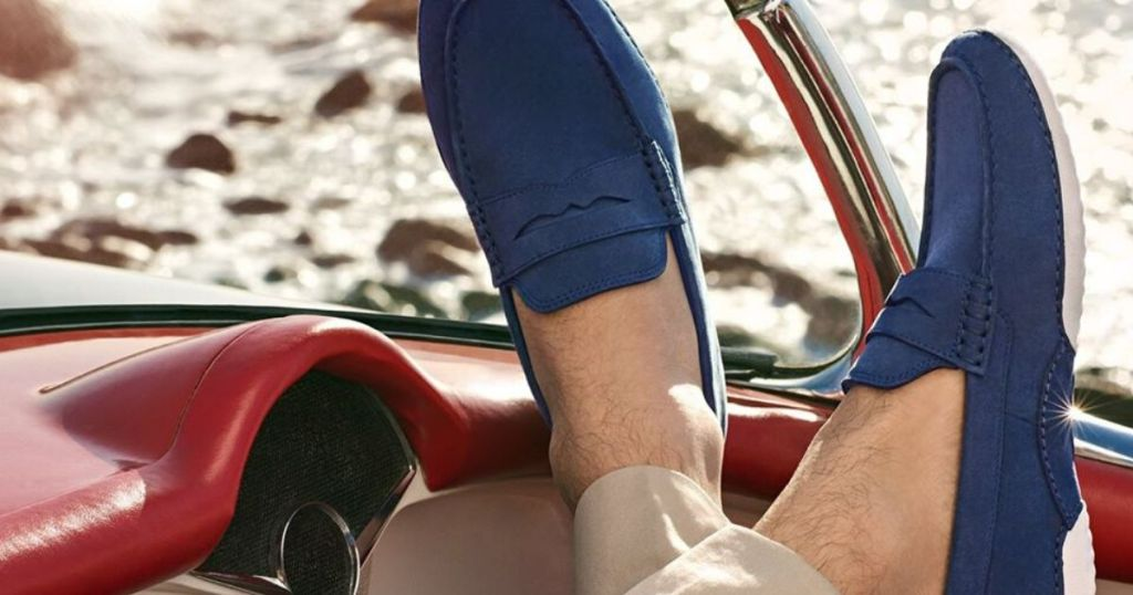 man wearing penny loafers with feet up on car dash